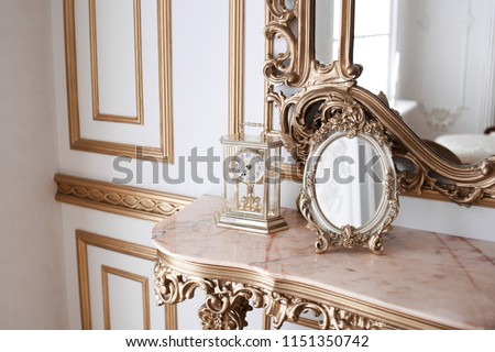 luxury mirror in gold frame. mirror on a vintage dressing table. Victorian-style. mechanic clock