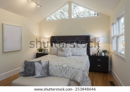 Luxury modern home bedroom with rug, view window and cherry wooden flooring with peaked roof with windows.