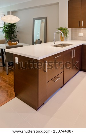 Luxury modern kitchen with dining table at the back. table. Interior design of a brand new house. Vertical.