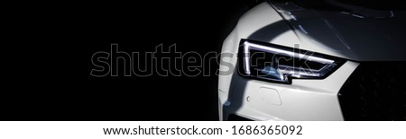 Luxury modern sport car with tinted headlights on black background. Copy space at left side. Car sales and tuning topic.