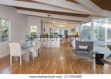 Luxury modern styled dining / living room area with open kitchen and outdoor view in inspirational contemporary home, villa.
