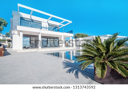 Luxury modern white house with large windows overlooking a Mediterian landscaped garden with palm trees and  blue swimming pool. High tech style villa. Vacation home or hotel. Modern loft design.ees a #1313743592