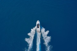 luxury motor boat. Aerial view of a boat in motion on blue water. Top view of a white boat sailing in the blue sea. Drone view of a boat sailing at high speed.