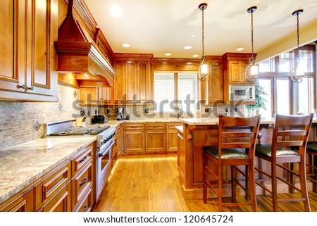 Luxury mountain home wood kitchen with island, granite and large stove.