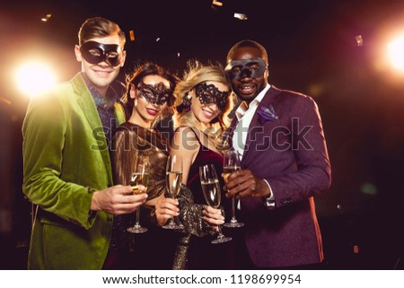 luxury multiethnic friends in carnival masks celebrating new year with champagne glasses