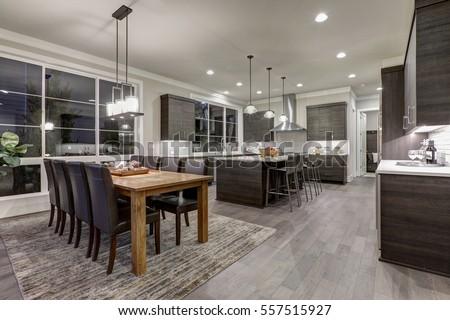 Photo of Luxury New construction home with open floor plan: dining and kitchen design. Rustic wood dining table matches with modern style leather chairs. Kitchen accented with dark cabinetry. Northwest, USA