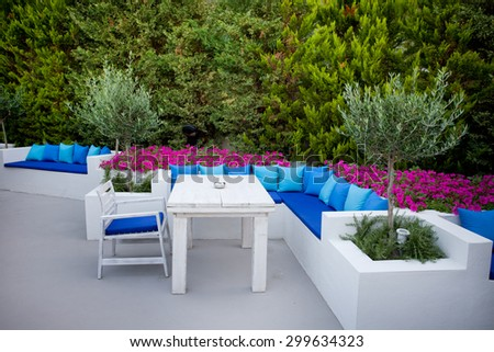 Luxury outdoor bar with white furniture and blue pillows in green environment
