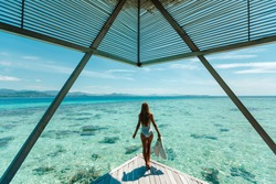 Luxury overwater bungalows Maldives resort woman going snorkeling from private hotel room island.  Travel vacation.  Aqua menthe trendy color of the new year 2020