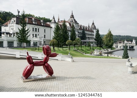 Luxury place. Monument of the dog made from balloons stands on the stand. Beautiful buildings, lake and forest at background. #1245344761