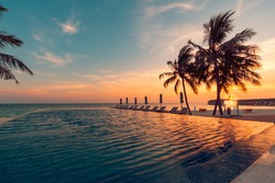Luxury pool sunset, palm tree silhouette with windy infinity pool water surface. Summer vacation, holiday template. Stunning sky, beachfront hotel resort at tropical landscape tranquil. Amazing island