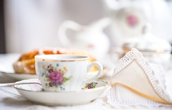 Luxury porcelain tea set with a cup, teapot, sugar bowl on white tablecloth with spongy cake on a plate