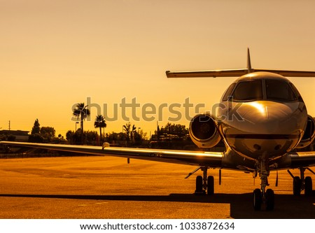 Luxury private jet is parked on an airfield during gorgeous golden sunset