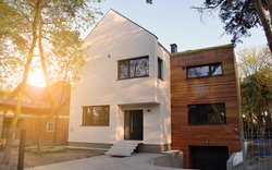 Luxury real estate single family house with wooden facade,  view during sunset.