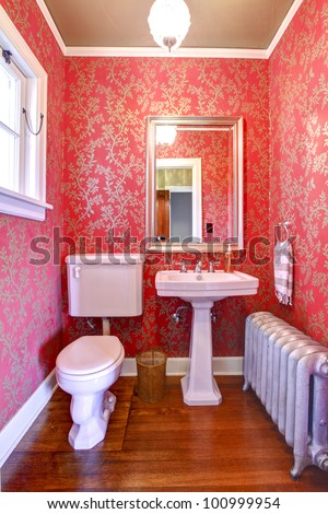 Luxury red and gold small bathroom with silver radiator.