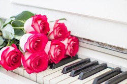 Luxury red roses on a piano. Bouquet of red roses and piano keys