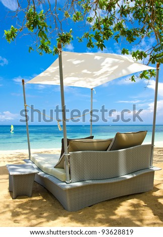 luxury relax chair on a beautiful tropical beach. blue sky and green plants