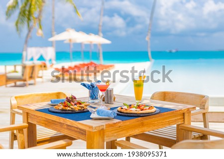Luxury resort hotel poolside, outdoor restaurant on the beach, ocean and sky, tropical island cafe, tables, food. Summer vacation or holiday, family travel. Palm trees, infinity pool, cocktails, relax