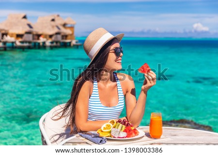 Luxury resort vacation woman eating fruits detox breakfast on beach hotel room with private terrace. Tourist girl healthy diet lifestyle.