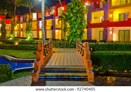 luxury resort with lazy river and bridge at night view