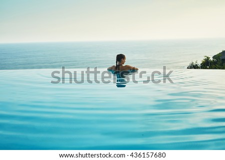Luxury Resort. Woman Relaxing In Infinity Swimming Pool Water. Beautiful Happy Healthy Female Model Enjoying Summer Travel Vacation, Looking At Sea View. Summertime Recreation, Relax And Spa Concept.