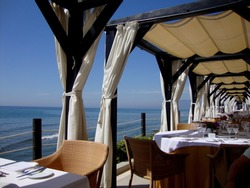 Luxury restaurant at the beach club in Marbella in Spain, with dining tables, chairs, cabanas and sea view