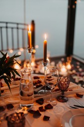 Luxury romantic candlelight dinner for couple. Table setup with candles and rose petals at night. Valentine decoration