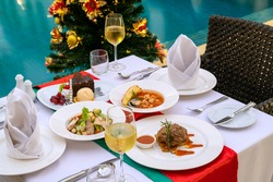 Luxury romantic dinner set up by the pool for couple on Christmas eve event.