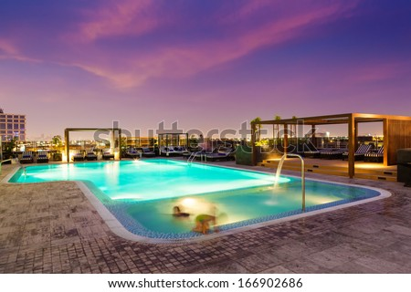Luxury rooftop swimming pool at sunset, blurred motion