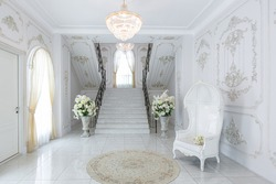 luxury royal posh interior in baroque style. very bright, light and white hall with expensive oldstyle furniture. chic wide marble staircase leading to the second floor