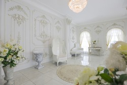 luxury royal posh interior in baroque style. very bright, light and white hall with expensive oldstyle furniture. large windows and stucco ornament decorations on the walls