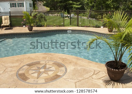 Luxury salt water pool and patio in a residential backyard.