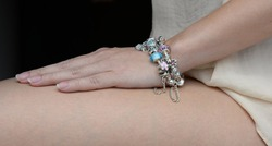 Luxury silver bracelet on women wrist. Bracelet in hand on women legs
