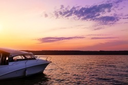 Luxury small fishing motorboat moored near lake or river coast at scenic evening with beautiful dramatic vibrant suset sky on background. Tranquil male leisure and adventure scene