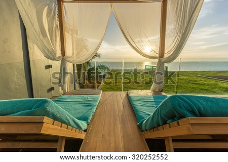 Luxury Spa Wood framed White Curtains Canopy Daybeds (Lounge chairs) Beach Tent on Grass Terrace near island Beach under Golden Sky Sunset in sea horizon in Summer in Resort at Pattaya, Thailand.