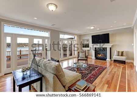 Luxury spacious family room interior with wall of glass doors leading out to spacious deck and facing the lake, polished hardwood floor and cozy sitting area with fireplace . Northwest, USA #566869141