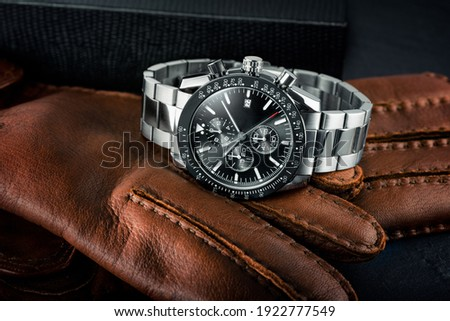 Luxury stainless steel chronograph watch resting on a pair of brown leather gloves. Nice man wrist watch with black dial. Dark toned.