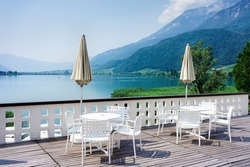 Luxury street restaurant at Caldaro Lake in South Tirol of Italy. Italian sidewalk cafe with tables and chairs and umbrellas at Kalterer See. Lifestyle terrace design and concept. Lakeview in summer.
