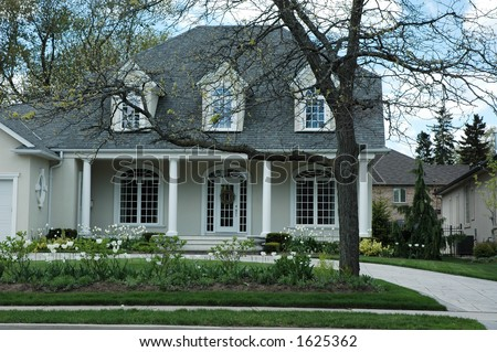 Luxury stucco house with white trim and bright green, manicured lawn / garden with white tulips and pillars by front porch