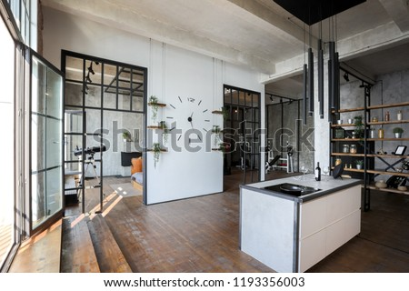 luxury studio apartment with a free layout in a loft style in dark colors. Stylish modern kitchen area with an island, cozy bedroom area with fireplace and personal gym #1193356003