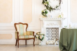 Luxury stylish bright light interior of sitting room. White walls decorated by ornament. Fireplace. Nobody inside room. Table setting by dishes, candles and flower bouquets.