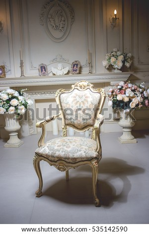 Luxury stylish bright light interior room. In the middle of the room chair. The white walls are decorated with ornaments. Fireplace. The flower vases bukety. Rich Baroque. #535142590
