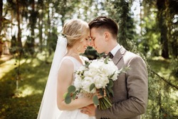 luxury stylish young bride and groom on the background spring sunny green forest. Couple in love.