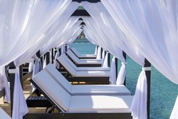 Luxury Sunbeds with White Curtains  Over the Sea.Summer Holiday Concept