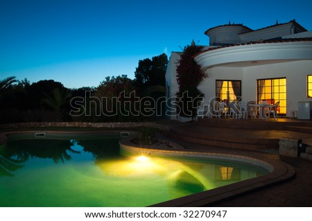 Luxury swimming pool and villa at night