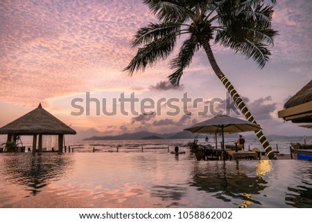 Luxury swimming pool in tropical resort, relaxing holidays in Seychelles islands. La Digue colorful pink orange sunset colors by the ocean, man in swim pool #1058862002