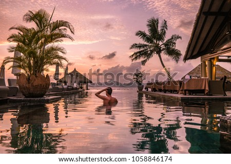 Luxury swimming pool in tropical resort, relaxing holidays in Seychelles islands. La Digue, Young man during sunset by swimpool