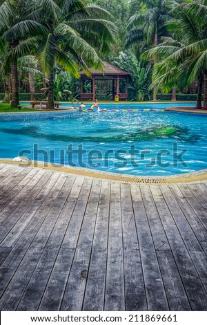 Luxury swimming pool with hut and wooden pool deck in garden of resort