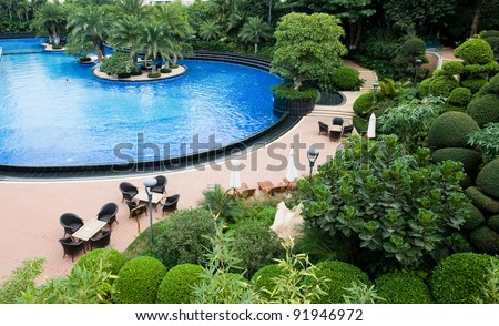 luxury swimming pool with shade trees.