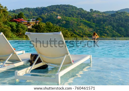 Luxury swimming pool with sunbeds in water at the resort with beautiful landscape view. #760461571