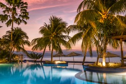 luxury swimmingpool on the beach during sunset with palms and reflections in the water, bali